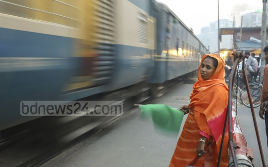 Gatekeeper Mukta Begum waves a green flag as a train passes by Tejgaon level-crossing in Dhaka on Saturday. Photo: Asif Mahmud Ove