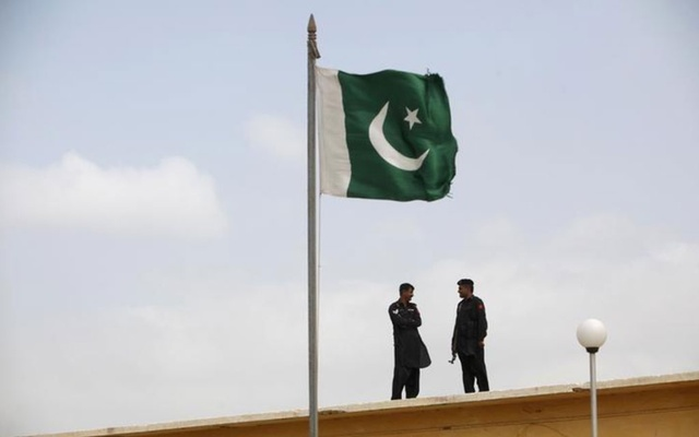 File Photo: A Pakistani flag flies on a mast as paramilitary Frontier Corps soldiers talk while guarding at Karachi's District Malir prison, Aug 23, 2013. REUTERS