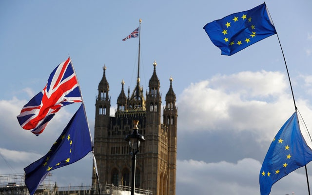 Flags representing Britain and the European Union flying over Parliament in London on Saturday. The New York Times