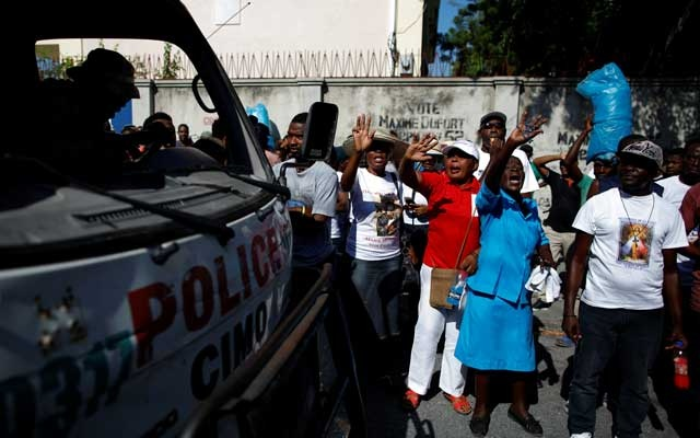 Faithful shout slogans next to a Haitian National Police truck outside of Christ Roi church before a march organised by religious leaders in Port-au-Prince, Haiti October 22, 2019. REUTERS