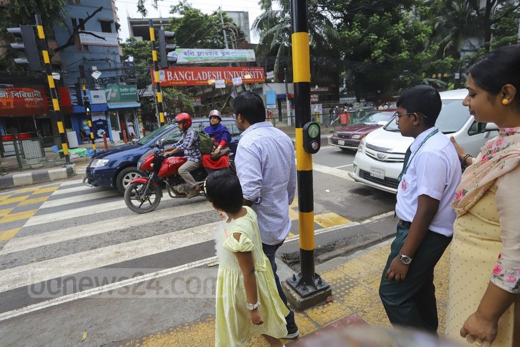Motorists are not taking notice of the red light after pedestrians pushed a button with countdown timer traffic signal in front of St Francis Xavier's Green Herald International School on Asad Avenue at Mohammadpur in Dhaka. Photo: Asif Mahmud Ove