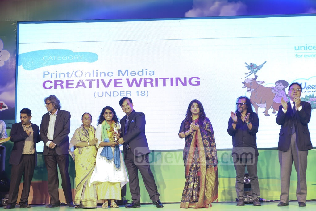 Pritha Pronodona, a child journalist of bdnews24.com's Hello, receiving the award after winning the third place in under-18 creative writing in print and online media category at a ceremony organised at Sonargaon Hotel on Sunday. Photo: Mahmud Zaman Ovi