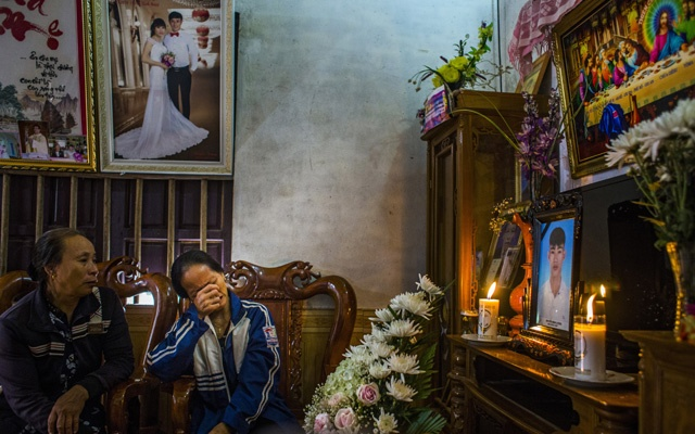 Nguyen Thi Huan, 55, weeps on Tuesday, Oct 29, 2019, in front of a photo of her son Nguyen Dinh Luong, in Can Loc, Vietnam. She fears he was among the 39 people found dead last week in a refrigerated truck container in Britain. The New York Times