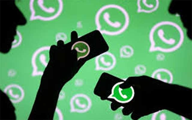 Men pose with smartphones in front of displayed Whatsapp logo in this illustration September 14, 2017. REUTERS