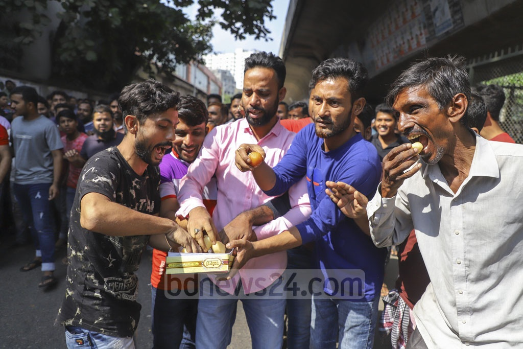 Residents offer sweets each other after the news on arrest of Dhaka South City Corporation Ward Councillor Moinul Haque Monju. Photo: Asif Mahmud Ove