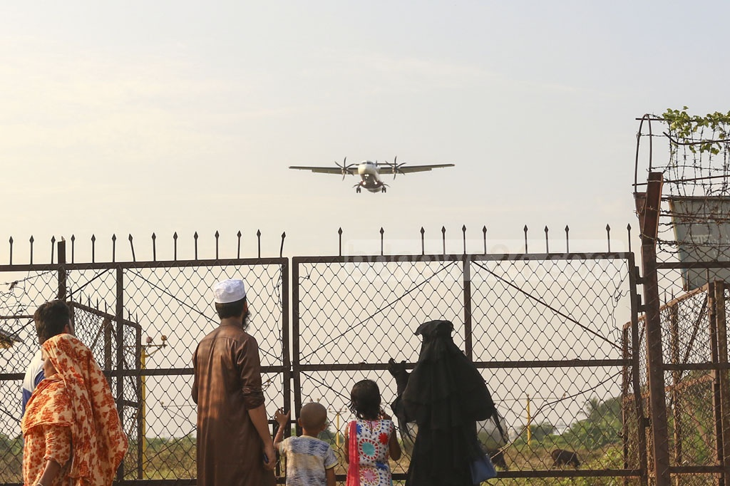 A family watching a plane fly on Baunia Road at Jasimuddin Road in Dhaka's Uttara next to Hazrat Shahjalal International Airport runway.