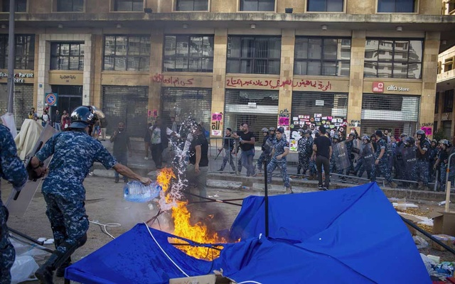 Lebanese policeman try to extinguish a fire with bottled water after a protest in Beirut on Tuesday, Oct. 29, 2019. Enormous antigovernment demonstrations in Iraq and Lebanon, some tinged with hostility toward Iran, have suddenly put Iran's interests at risk. (Diego Ibarra Sanchez/The New York Times)