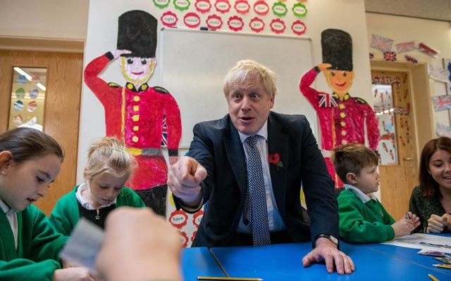 Prime Minister Boris Johnson looking at old photographs of London with students at Abbots Green Primary Academy in Bury St Edmunds, Britain. The New York Times