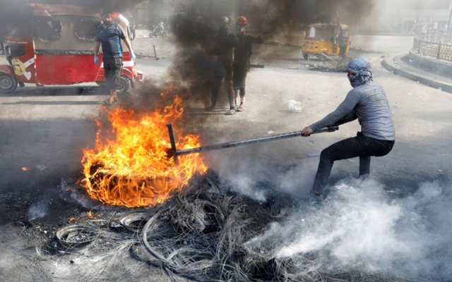 An Iraqi demonstrator pulls a burnt tire as he blocks the road during ongoing anti-government protests, in Baghdad, Iraq Nov 3, 2019. REUTERS
