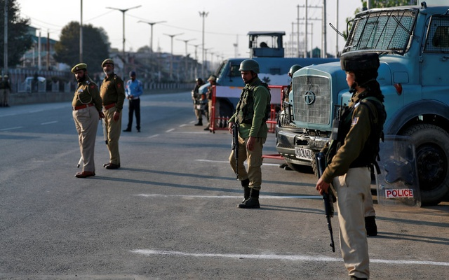 FILE PHOTO: Indian policemen stand guard on a road in Srinagar Oct 31, 2019. REUTERS