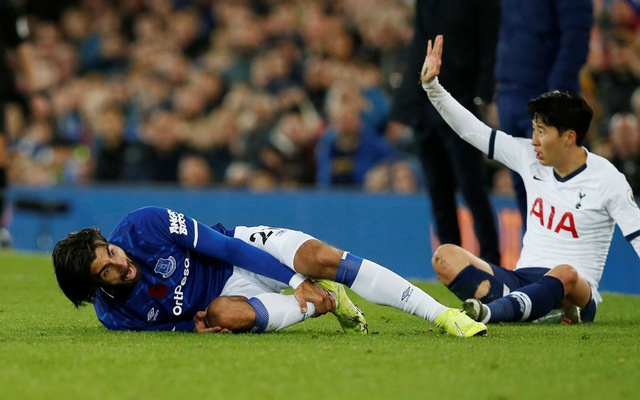 Football - Premier League - Everton v Tottenham Hotspur - Goodison Park, Liverpool, Britain - November 3, 2019 Everton's Andre Gomes reacts after sustaining an injury as Tottenham Hotspur's Son Heung-min gestures REUTERS