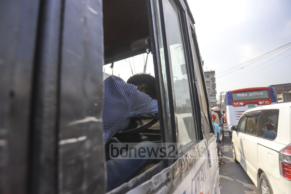 The driver of a small passenger vehicle sleeping with his head on the steering during traffic gridlock on English Road on Tuesday as it takes around an hour to cross the two kilometres from Gulistan to Sadarghat in Dhaka. Photo: Asif Mahmud Ove