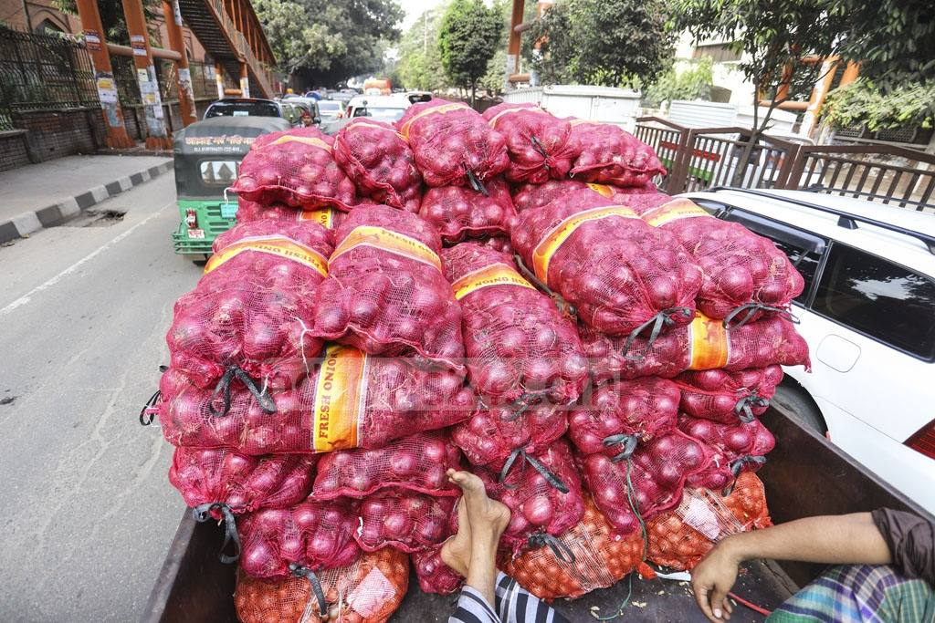 Traders transporting onion imported from Egypt after buying the cooking ingredient from Old Dhaka's Shyambazar wholesale market at Tk 90 per kg on Tuesday. Photo: Asif Mahmud Ove