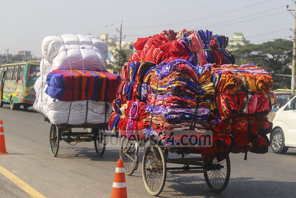 A rickshaw-van is carrying the blankets made from factories around Dhaka to the wholesale market for sale before the winter sets in. Photo: Asif Mahmud Ove
