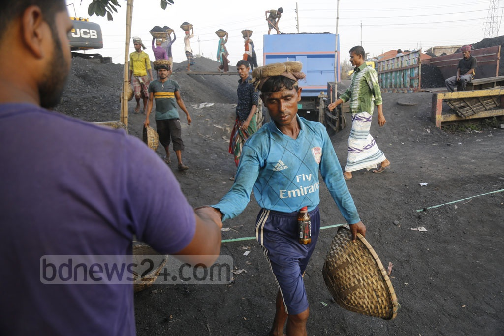Workers are collecting tokens after emptying coal-filled baskets. Photo: Mahmud Zaman Ovi