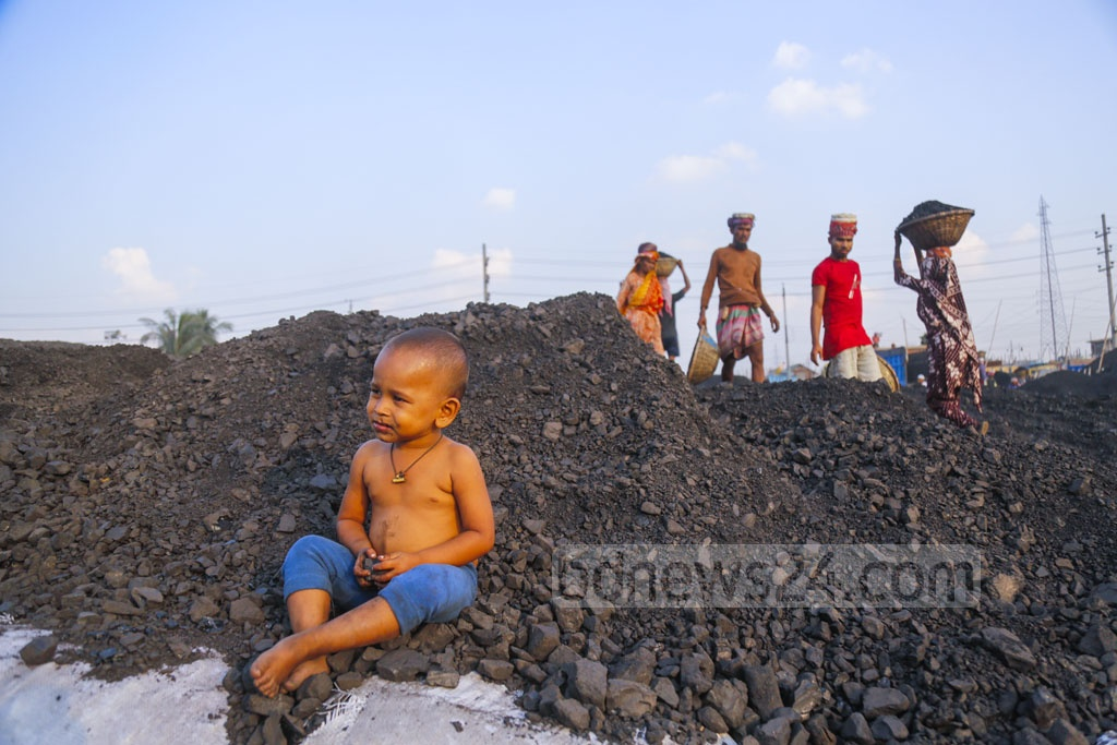 A child is playing on coal while its parents work. Photo: Mahmud Zaman Ovi