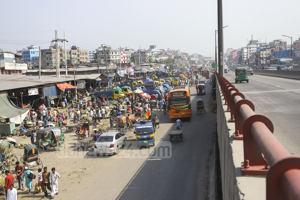 Trucks parked in front of the market occupy a chunk of the road beneath the flyover in Dhaka's Jatrabari. Photo: Asif Mahmud Ove