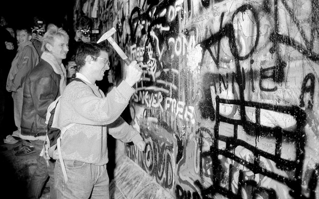 FILE PHOTO: A man hammers a section of the Berlin Wall near the Brandenburg Gate after the opening of the East German border was announced in Berlin, November 9, 1989. REUTERS