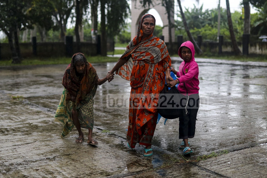 Family of nonagenarian Joytun arrives at Mongla Port High School, which has been turned into a temporary storm shelter, in Bagerhat on Saturday as Cyclone Bulbul nears the coast. Photo: Mostafigur Rahman
