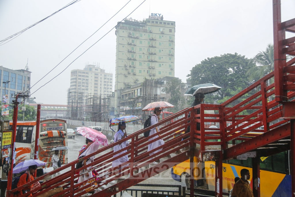 People carry umbrellas in Dhaka on Saturday to protect themselves from rains triggered by Cyclone Bulbul. Photo: Mahmud Zaman Ovi