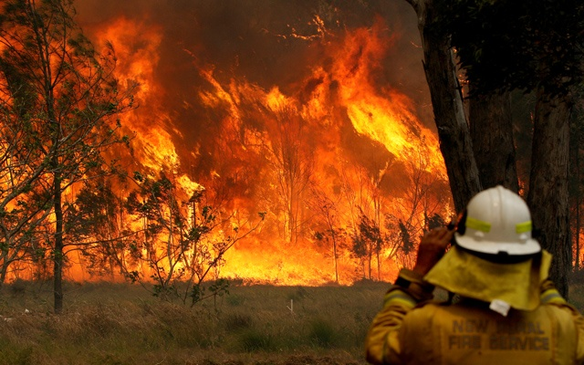 A firefighter on property protection watches the progress of bushfires in Old Bar, New South Wales, Australia Nov 9, 2019. REUTERS