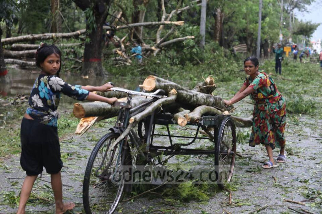 Local residents removed trees uprooted by the cyclone storm on the Mongla- Bagerhat Highway. Photo: Mostafigur Rahman