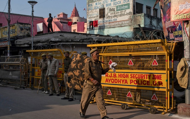 A police officer walks past a security barricade as others stand guard near a temple after Supreme Court's verdict on a disputed religious site, in Ayodhya, India, Nov 10, 2019. REUTERS