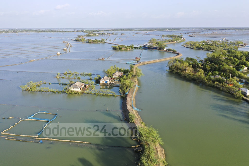 Homes and fish enclosures are damaged as storm surges triggered by Cyclone Bulbul inundate Shyamnagar Upazila's Gabura Union after breaching the embankments. Photo: Mostafigur Rahman