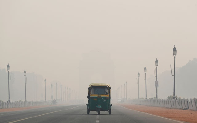 An auto-rickshaw moves past the India Gate on a smoggy morning in New Delhi, India Nove 11, 2019. REUTERS