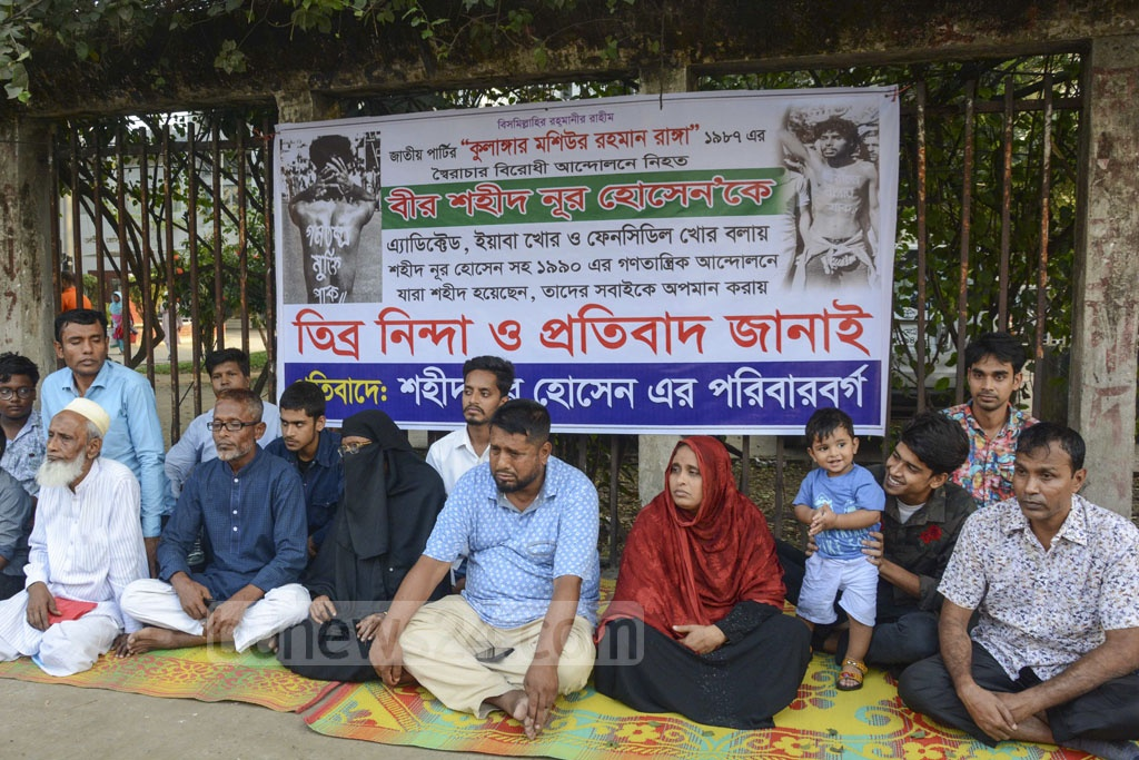 The family of Nur Hossain staging a sit-in protest in front the National Press Club on Monday after the pro-democracy activist, martyred while protesting against the autocratic rule of HM Ershad, was labelled a drug addict by Jatiya Party Secretary General Moshiur Rahman Ranga.