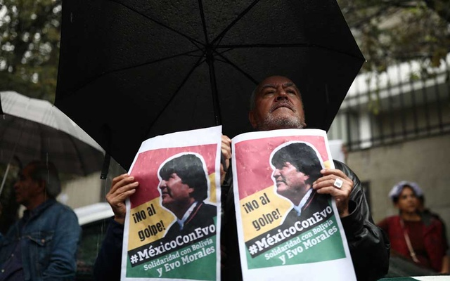 A man holds a sign during a demonstration in support of Bolivian President Evo Morales after he announced his resignation on Sunday, outside the Bolivian Embassy in Mexico City, Mexico, Nov 11, 2019. The sign reads,
