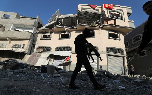 A Palestinian militant walks past the home of Islamic Jihad field commander Baha Abu Al-Atta after it was hit by an Israeli strike that killed him in Gaza City Nov 12, 2019. REUTERS