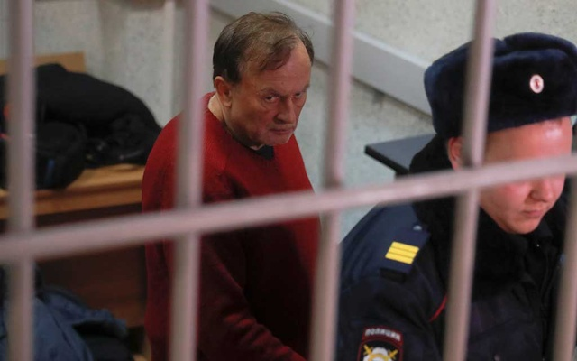Russian historian and professor Oleg Sokolov, who is accused of murdering his girl friend and former student, is escorted inside a court building in Saint Petersburg, Russia Nov 11, 2019. REUTERS