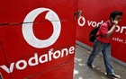 FILE PHOTO: A man speaks on his mobile phone as he walks past logos of Vodafone painted on a roadside wall in Kolkata May 20, 2014. Reuters