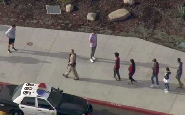 A law enforcement official leads students at the scene of a shooting at Saugus high school in Santa Clarita, California, US, November 14, 2019 in this screenshot taken from video footage courtesy of NBCLA. NBCLA via REUTERS
