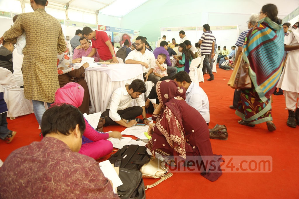 Many sat on the floor to fill out forms as the seats were already occupied at the crowded Income Tax Fair at the Officers' Club in Dhaka on Friday. Photo: Mahmud Zaman Ovi