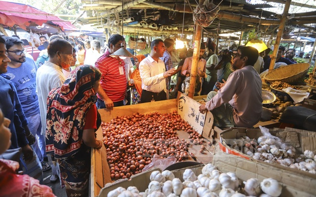 Officials speaking to traders and customers during a mobile court by the Directorate of National Consumer Rights Protection on the Mirpur-6 kitchen market in Dhaka on Friday to keep onion prices down. Photo: Asif Mahmud Ove