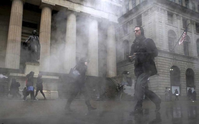 FILE PHOTO: Morning commuters walk through a steam cloud on Wall St. during a morning snow fall in New York's financial district March 4, 2016. Reuters