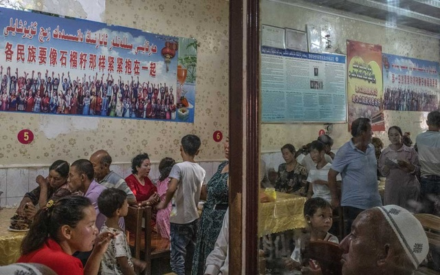 "Patrons dine under posters quoting Xi Jinping, reading ""every ethnic group must tightly bind together like the seeds of a pomegranate,"" at a restaurant in Yarkand, in China's Xinjiang province, Aug 5, 2019. The New York Times"