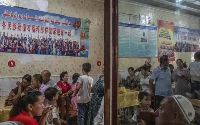 """Patrons dine under posters quoting Xi Jinping, reading """"every ethnic group must tightly bind together like the seeds of a pomegranate,"""" at a restaurant in Yarkand, in China's Xinjiang province, Aug. 5, 2019. Leaked documents have provided an unprecedented inside look at China's crackdown in Xinjiang. (Gilles Sabrié/The New York Times)"""