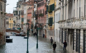 People walk in a flooded street during a period of seasonal high water in Venice Venice, Italy, Nov 17, 2019. REUTERS/Manuel Silvestri