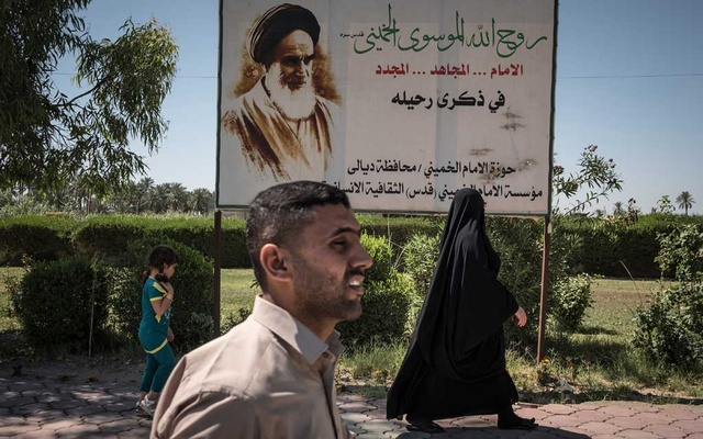 FILE - Iraqis walk past a poster of Ayatollah Ruhollah Khomeini, the founder of the Islamic Republic of Iran, in Diyala, Iraq on Sunday, Jun 4, 2017. (Sergey Ponomarev/The New York Times)