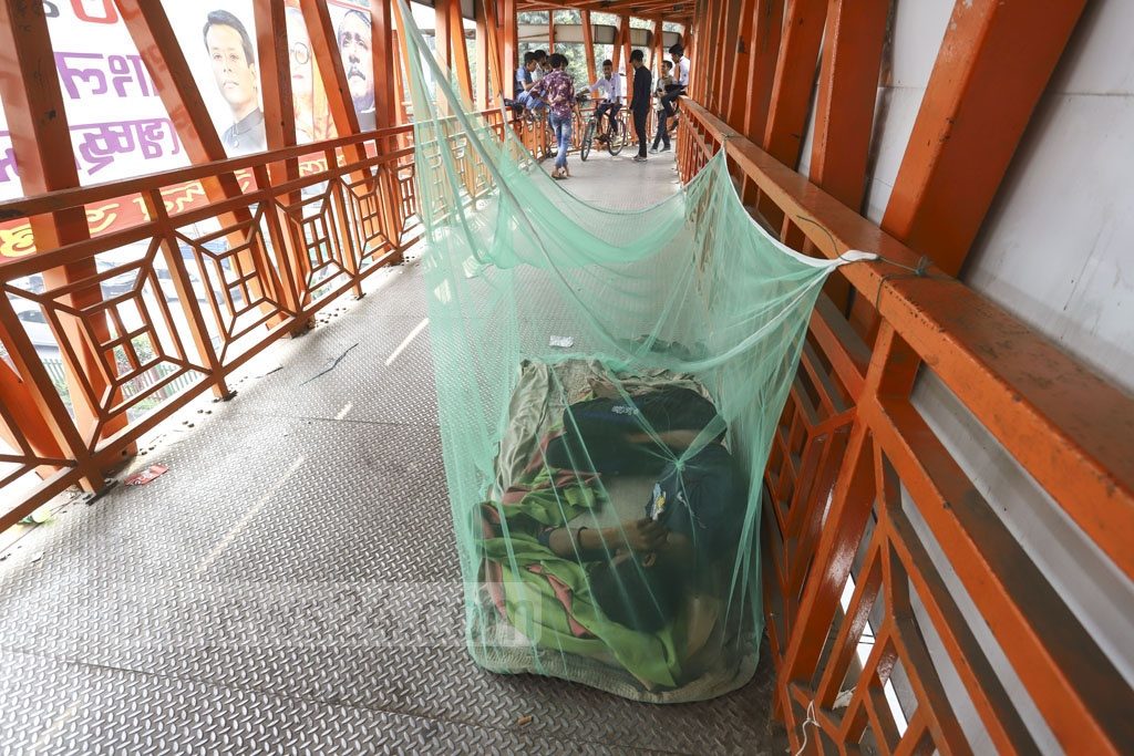 A man sleeps inside a mosquito net on a footbridge used by school children to cross the road in Dhaka's Mirpur-13. Photo: Asif Mahmud Ove
