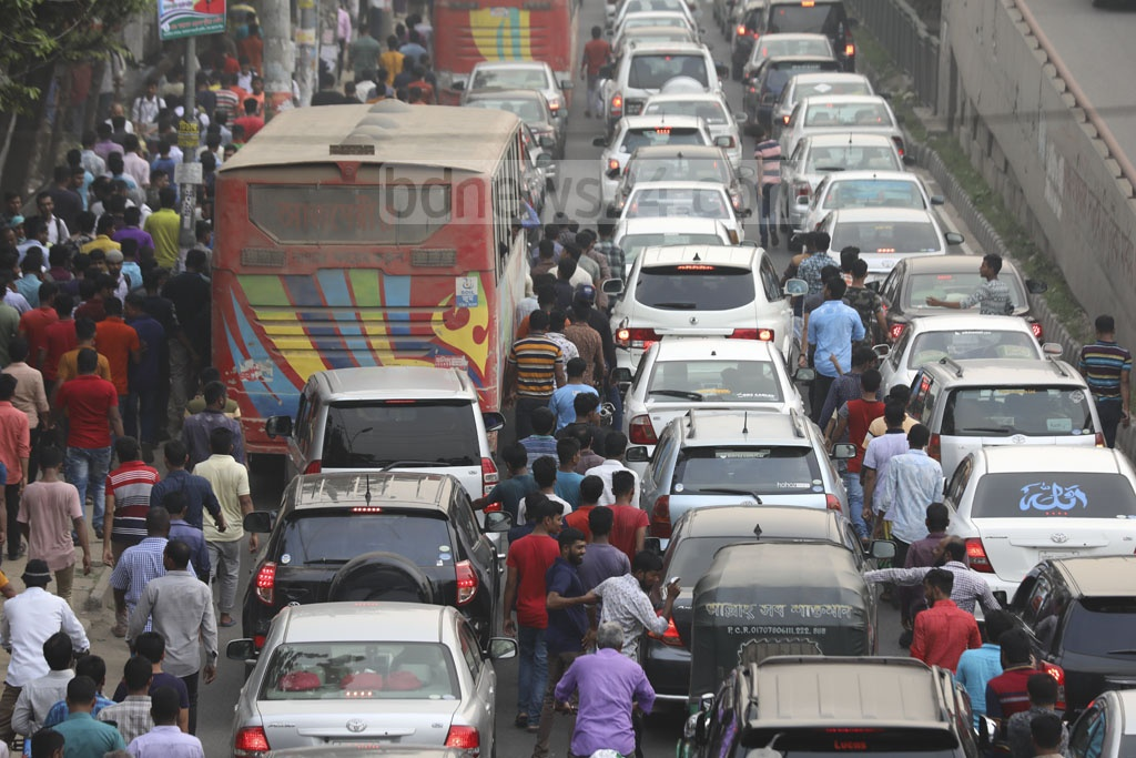 Transport workers protesting a new transport law occupy a key road through Dhaka's Tejgaon on Tuesday, creating a long tailback.