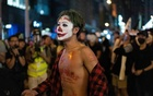 A protester with Joker-inspired face paint shouts slogans at police in Hong Kong, Oct 31, 2019. The New York Times