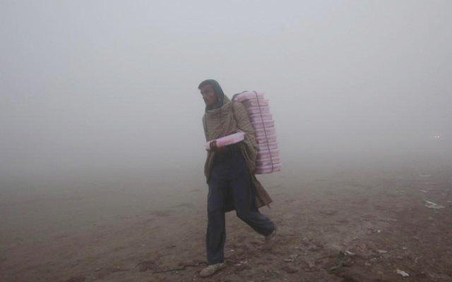A vendor carries plastic boxes on a smoggy morning in Lahore, Pakistan Jan 3, 2019. REUTERS