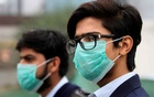 Men wearing protective masks wait for a bus in Lahore, Pakistan November 22, 2019. REUTERS