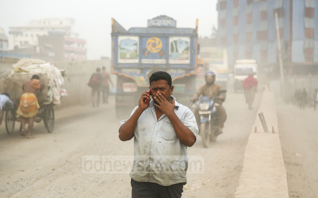 People cover their noses and mouths to protect themselves from dust on a street at Postogola in Dhaka. Photo: Mahmud Zaman Ovi