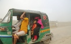 A woman on an autorickshaw covers the nose of a child to save it from dust on a street at Postogola in Dhaka. Photo: Mahmud Zaman Ovi