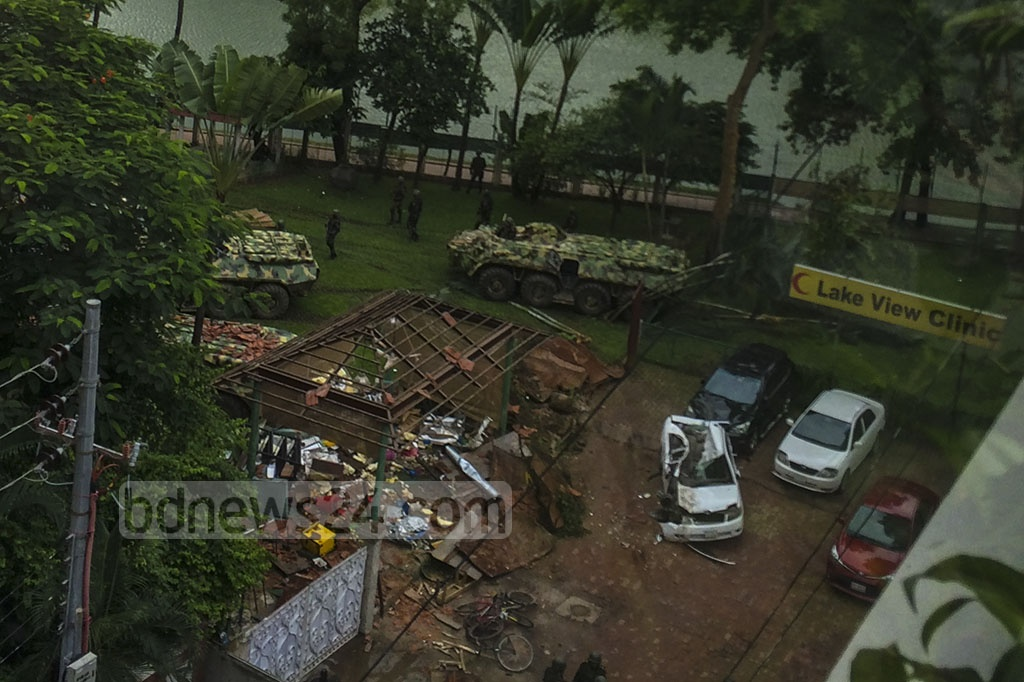 Armoured vehicles storm Holey Artisan after tearing down one side of the restaurant's boundary wall.